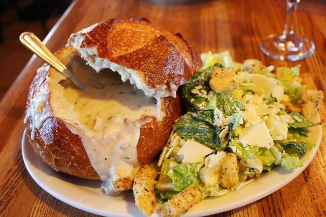 La gustosa zuppa di molluschi servita all'interno di una pagnotta fresca e accompagnata dalla Caesar salad del Pier Market seafood restaurant. Foto Grigore Scutari
